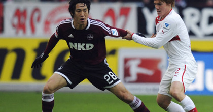 Japanese history in Germany: Nuremberg's Mu Kanazaki is held by Gotoku Sakai of Stuttgart as four Japanese players appeared in the game - a new record. Photo by Getty Images